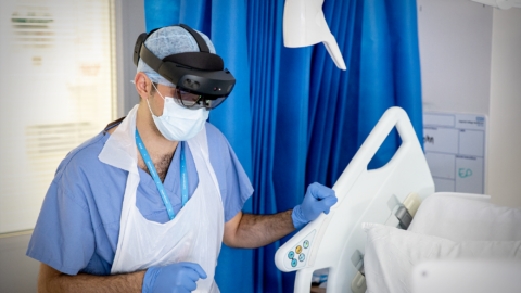 An NHS doctor at St. Mary's Hospital speaks with a patient on a COVID-19 ward during the pandemic whilst wearing a Microsoft HoloLens 2