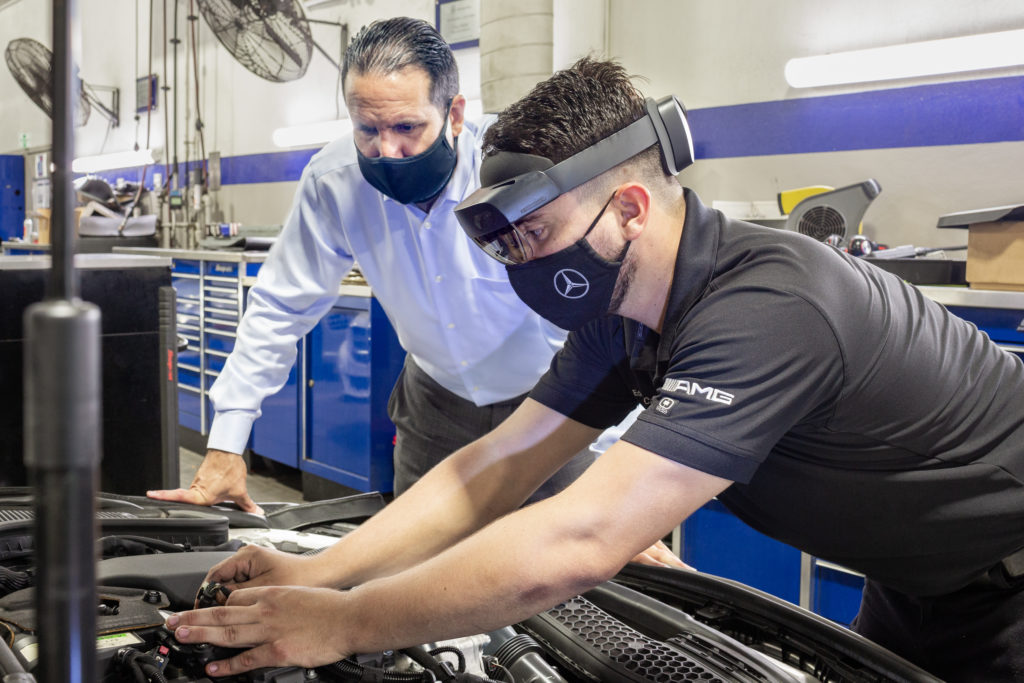 An auto repair technician wearing a HoloLens 2 and a face mask works with his hands on a Mercedes-Benz car engine while his supervisor, in a face mask, watches over his shoulder.