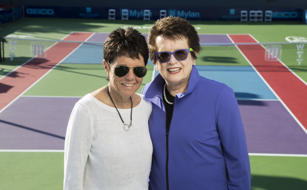 Ilana Kloss stands to the left of Billie Jean King with a tennis court in the background.