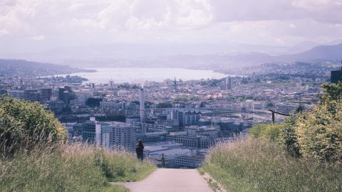 The city of Zurich sits below a bank of clouds. In the fore ground, a road is flanked by green grass.