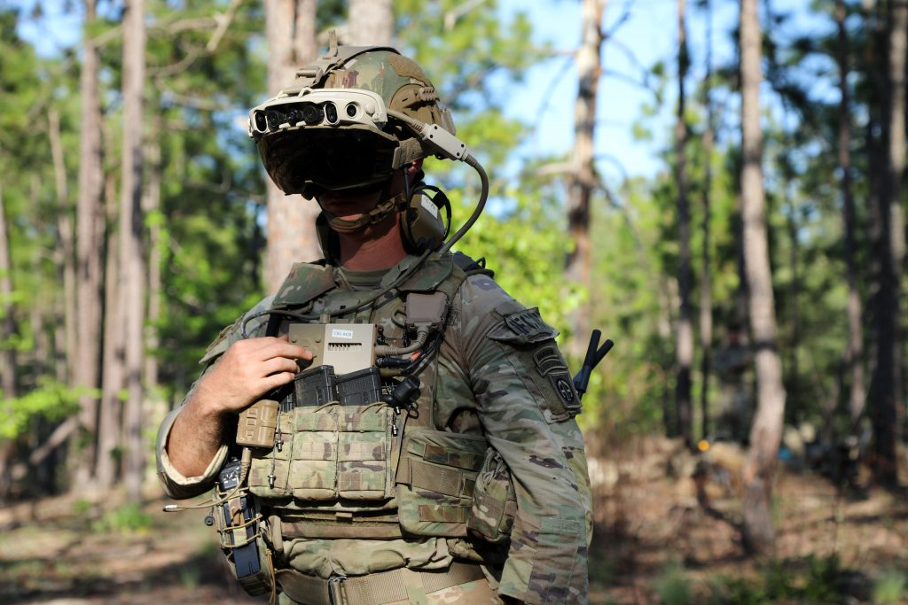 Photo of a soldier in a wooded area, wearing a mixed-reality headset during testing.