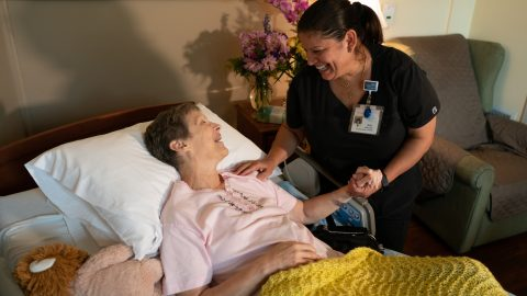 Photo of a caregiver bending over a female hospice patient in a bed.