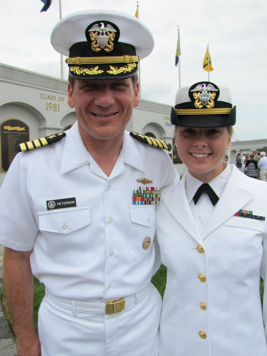 man in naval uniform smiles with his daughter, also in naval uniform