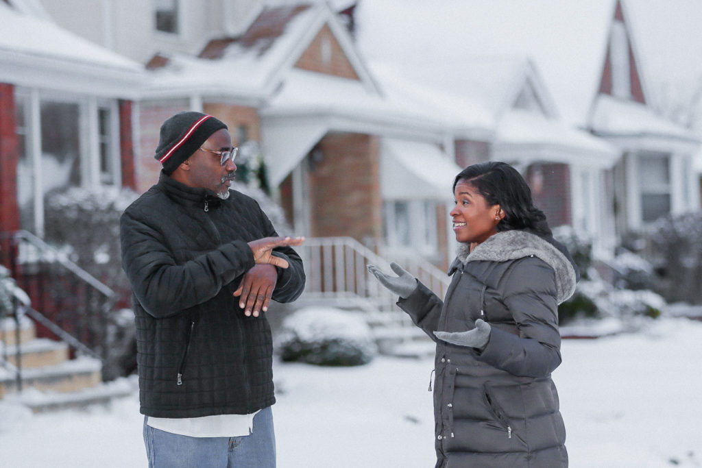 Royce Martin and Heather Dowdy having a conversation while standing in the snow outside their family home in Chicago.