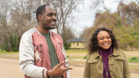 A man and a woman laugh together as they stand outside a vacant lot