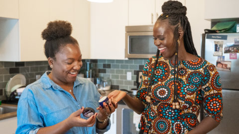 Two women in a kitchen laughing as they hold a jar of shea butter