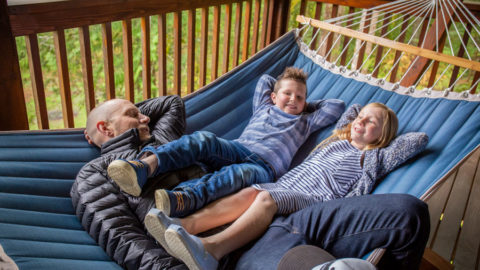 A man lays on a hammock with his children, a boy and a girl, who hang their legs over his lap