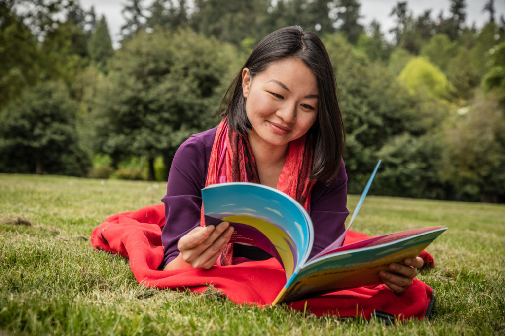 A photo of a woman lying on a blanket in the grass reading a book