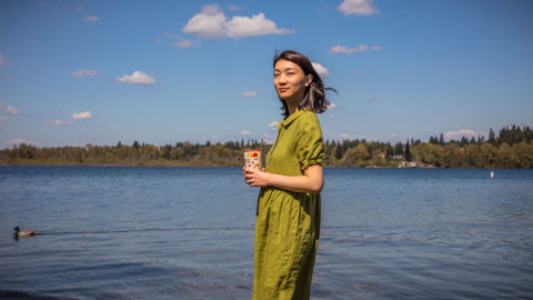 A woman in a green dress who is holding a coffee cup and standing at the shore of a lake
