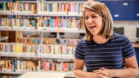 A woman smiling while standing in a school library with a shelf of books behind her
