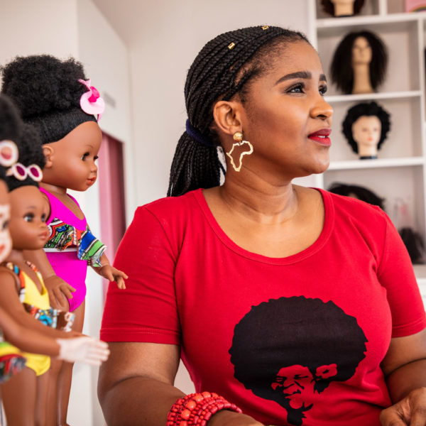 A woman looks thoughtfully to the side while standing by the dolls she made