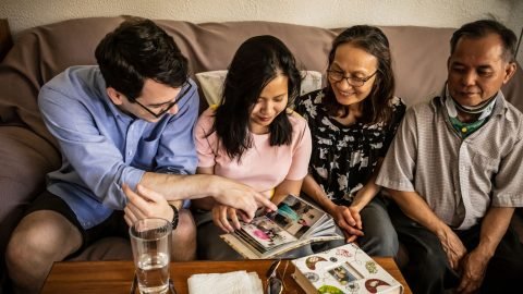 Huong Haley sitting on a couch with her husband and her parents, looking at scrapbook photos together