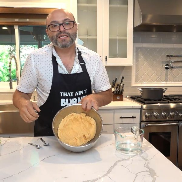 A man wearing an apron holds a pan of dough