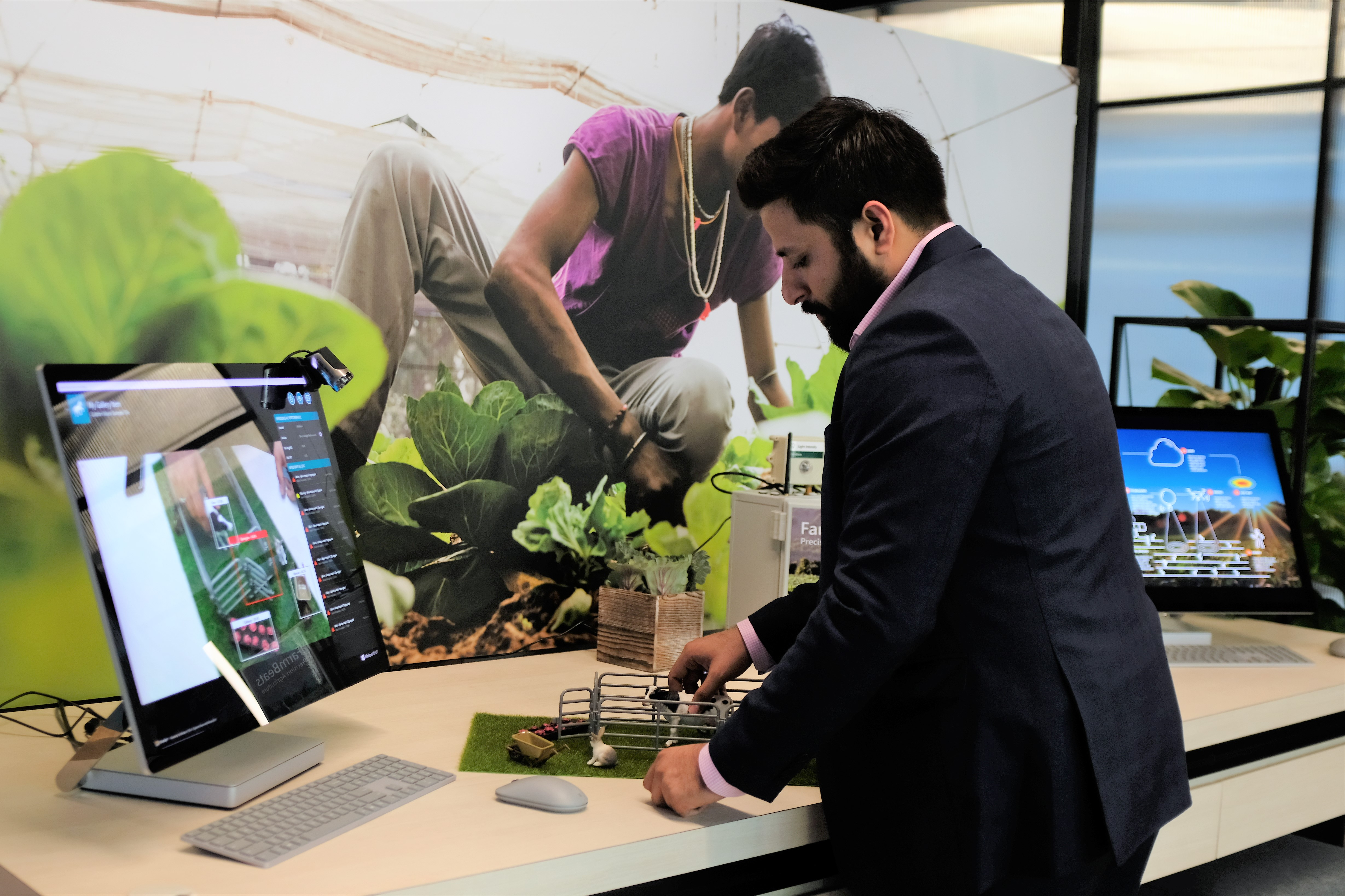 A man with model farm animals in front of a PC screen.