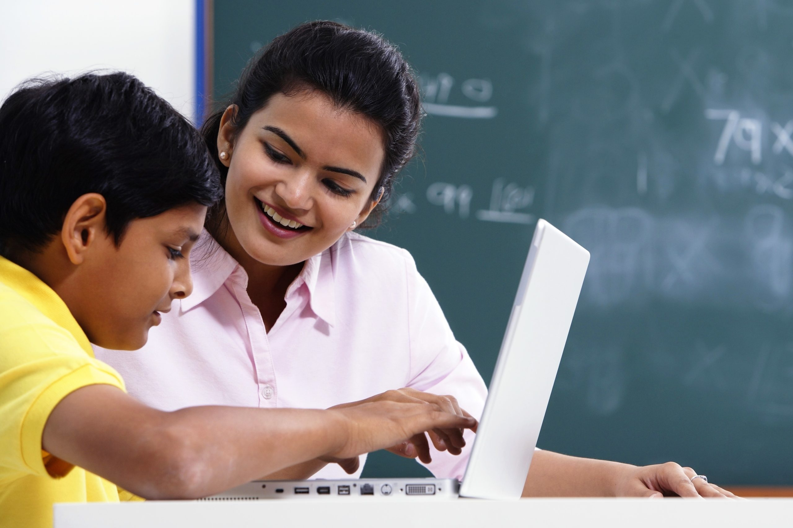 A teachers and student look at a laptop