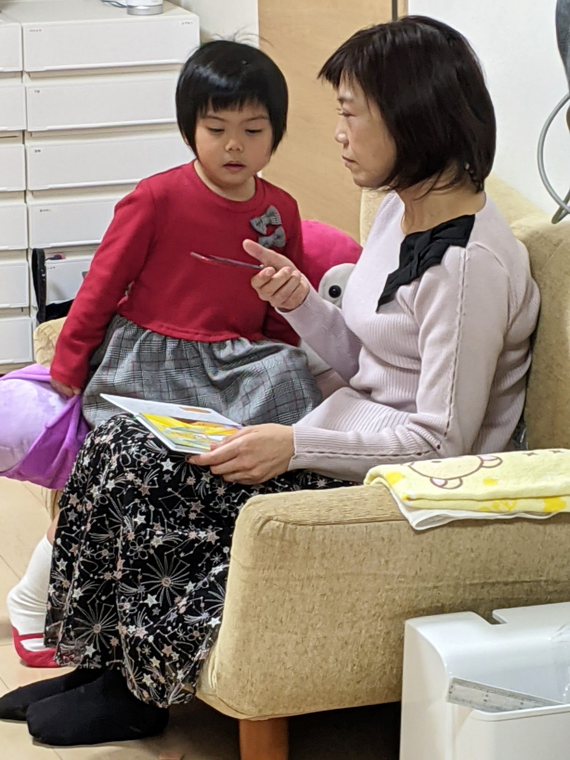 A mother and young daughter read a book