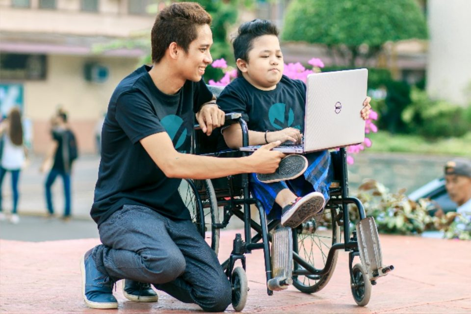 A man kneels and another man sits in a wheelchair