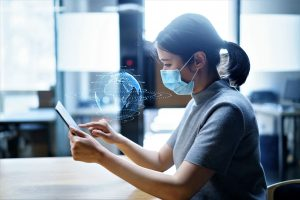 A woman wearing a mask uses her handheld device