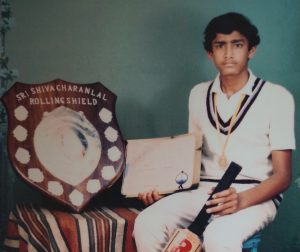 A boy poses with an award shield and cricket bat