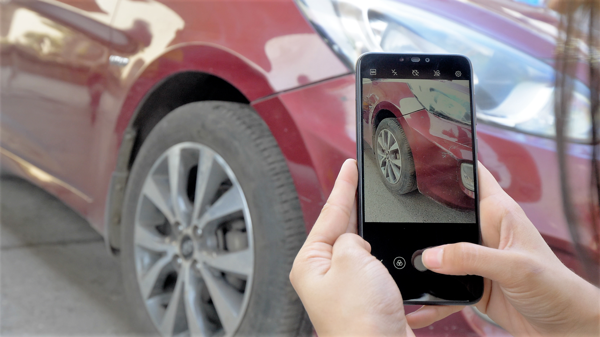 A person clicking snapshot of a car's tyre