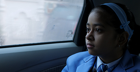 A 13 year old girl dressed in school uniform, seated in a car and looking out of the car window