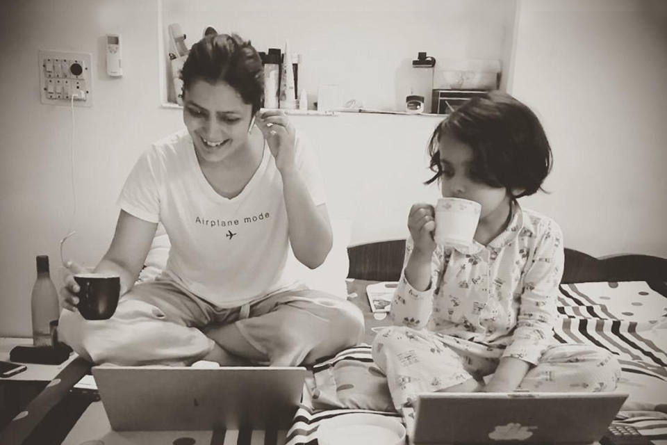 A woman working from home on her laptop, as her daughter looks on and imitates her actions on a toy laptop.