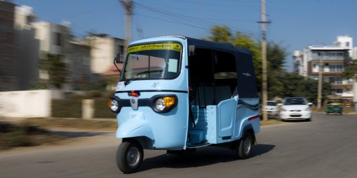 Photo of a blue-colored autorickshaw on a road.