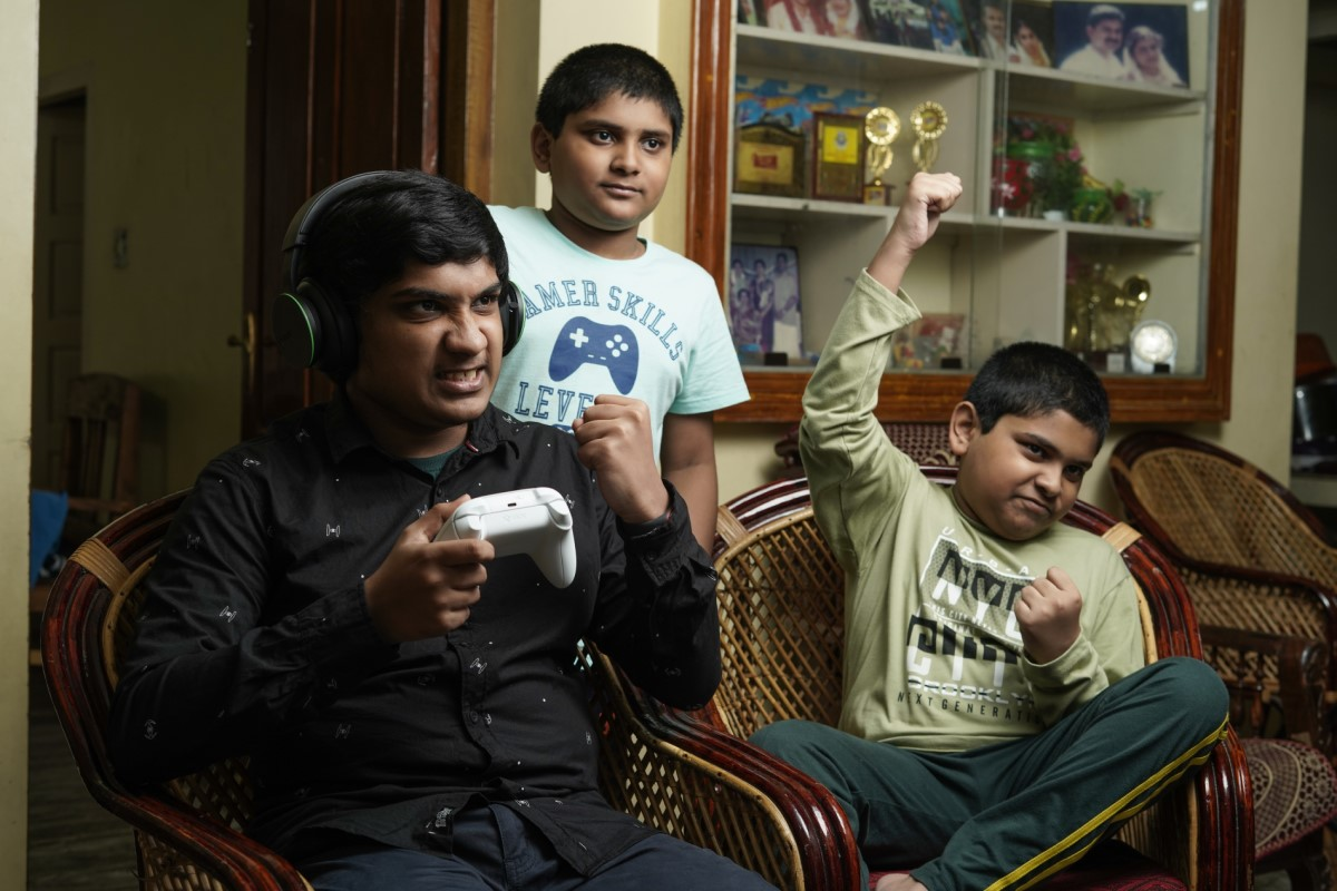 a photo of three boys celebrating while playing an xbox game