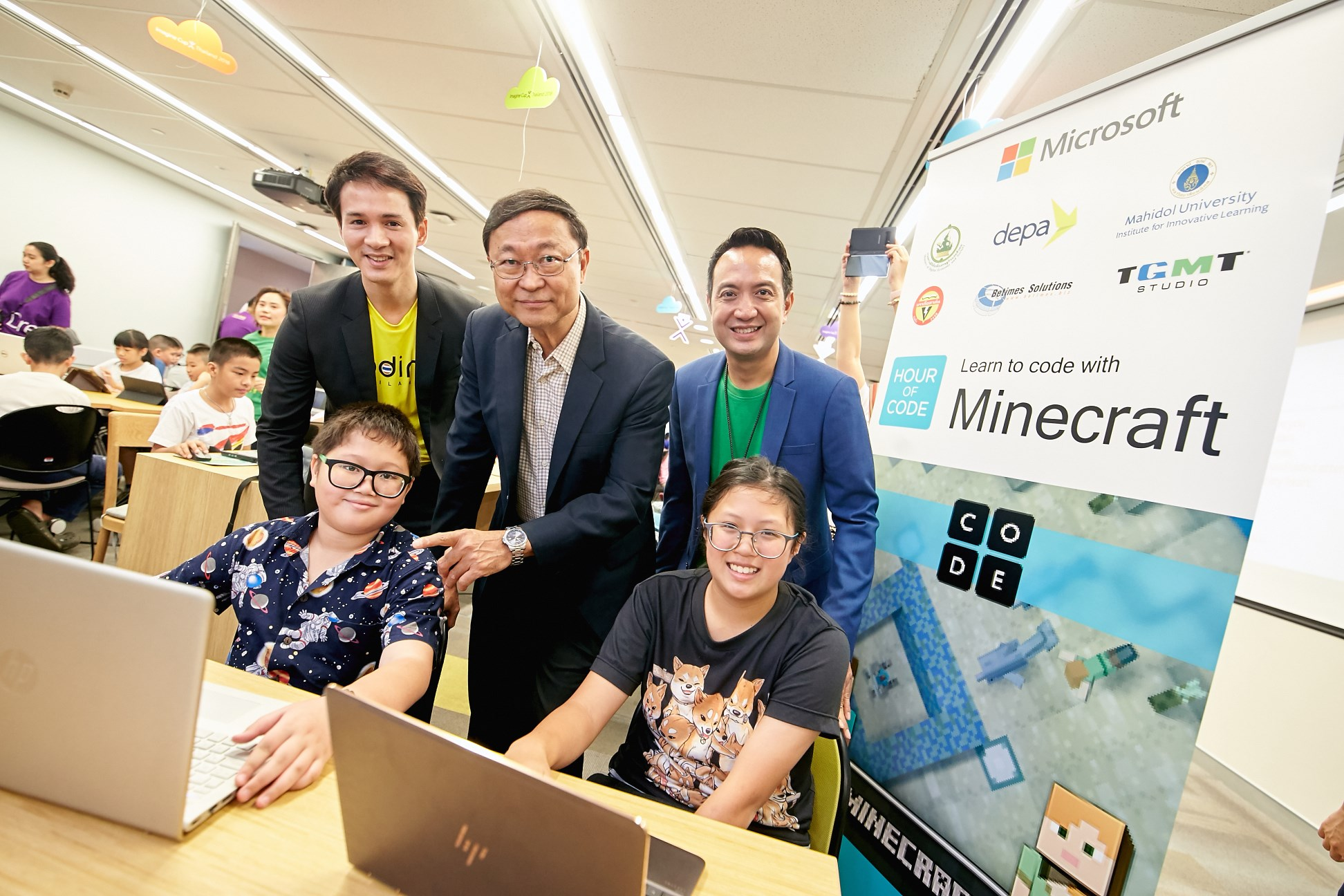 Executives and children in coding activity