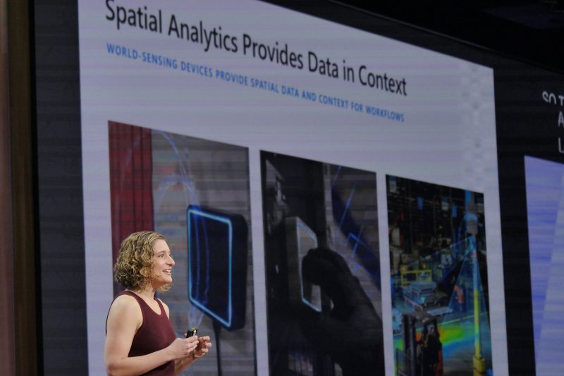 "Photo of woman standing on stage in front of a screen that reads ""Spatial Analytics Provides Data in Context."""