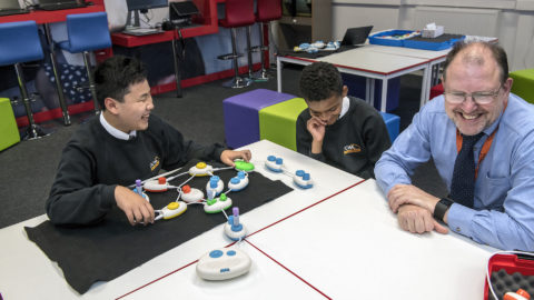 Daniel and Rico sit smiling at a table with a string of plastic pods, also with a smiling Jonathan Fogg