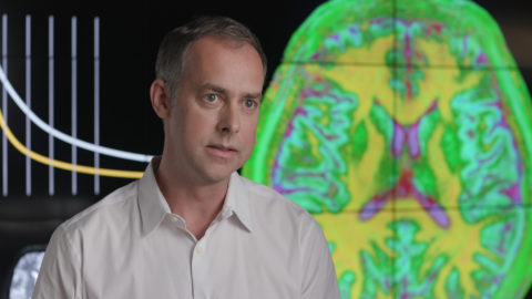 Mark Griswold talks to an interviewer in front of a screen showing MRI scans of a human brain