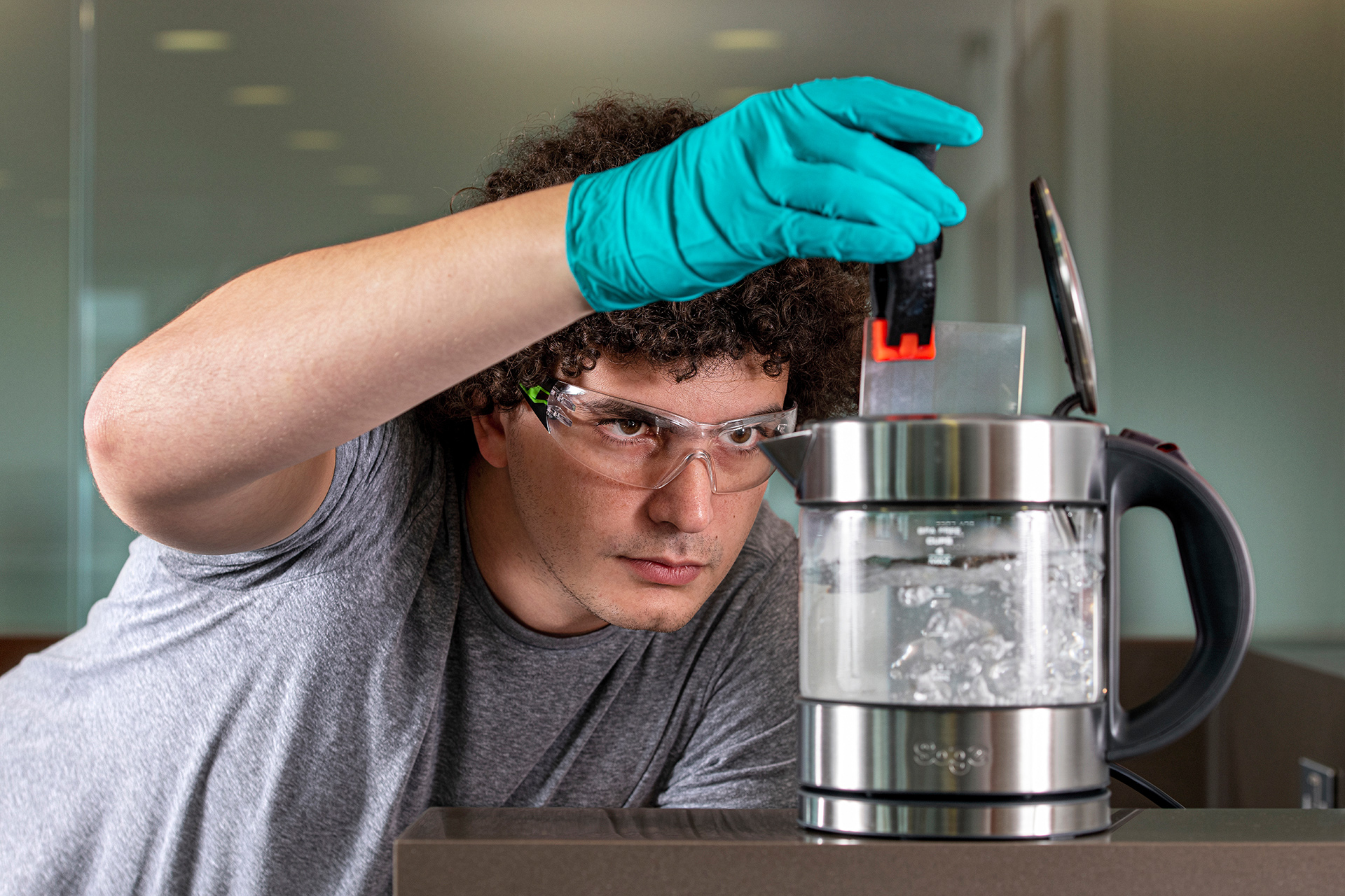 Researcher Youssef Assaf drops a square of silica glass in a kettle of boiling water to demonstrate its durability
