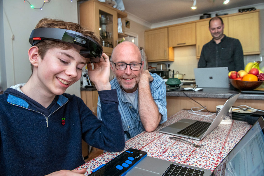 Theo smiles with his left hand touching a HoloLens that sits on his head, while interacting with Microsoft researchers at a kitchen table