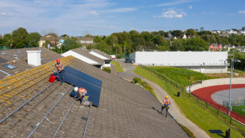 Men on a school roof installing solar panels
