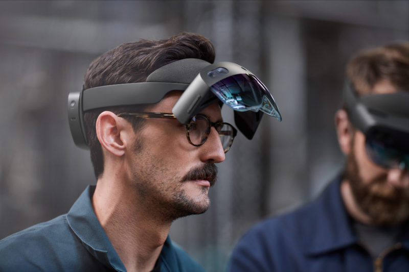 A man wearing a HoloLens 2 has the visor flipped up