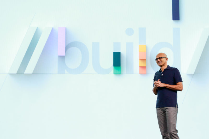 "Satya Nadella stands on stage, hands clasped in front of a sign that says ""Build"""