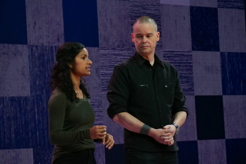 A woman and a man stand on stage speaking