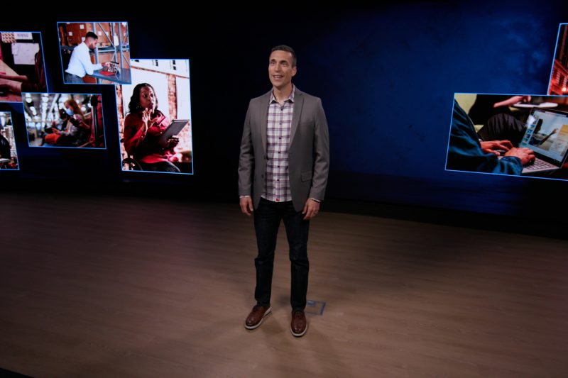 Jared Spataro standing in a room with screens behind him