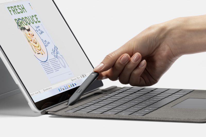 A person holding a Slim Pen 2 next to a Surface Pro 8