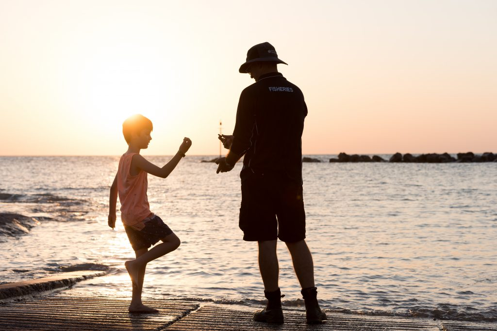 Photo of Shane Penny with his son on a Darwin beach