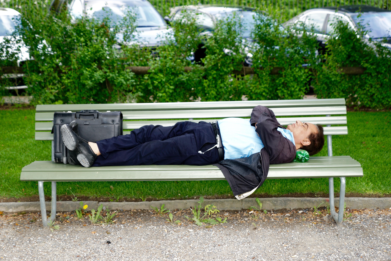 Businessman asleep on bench in park