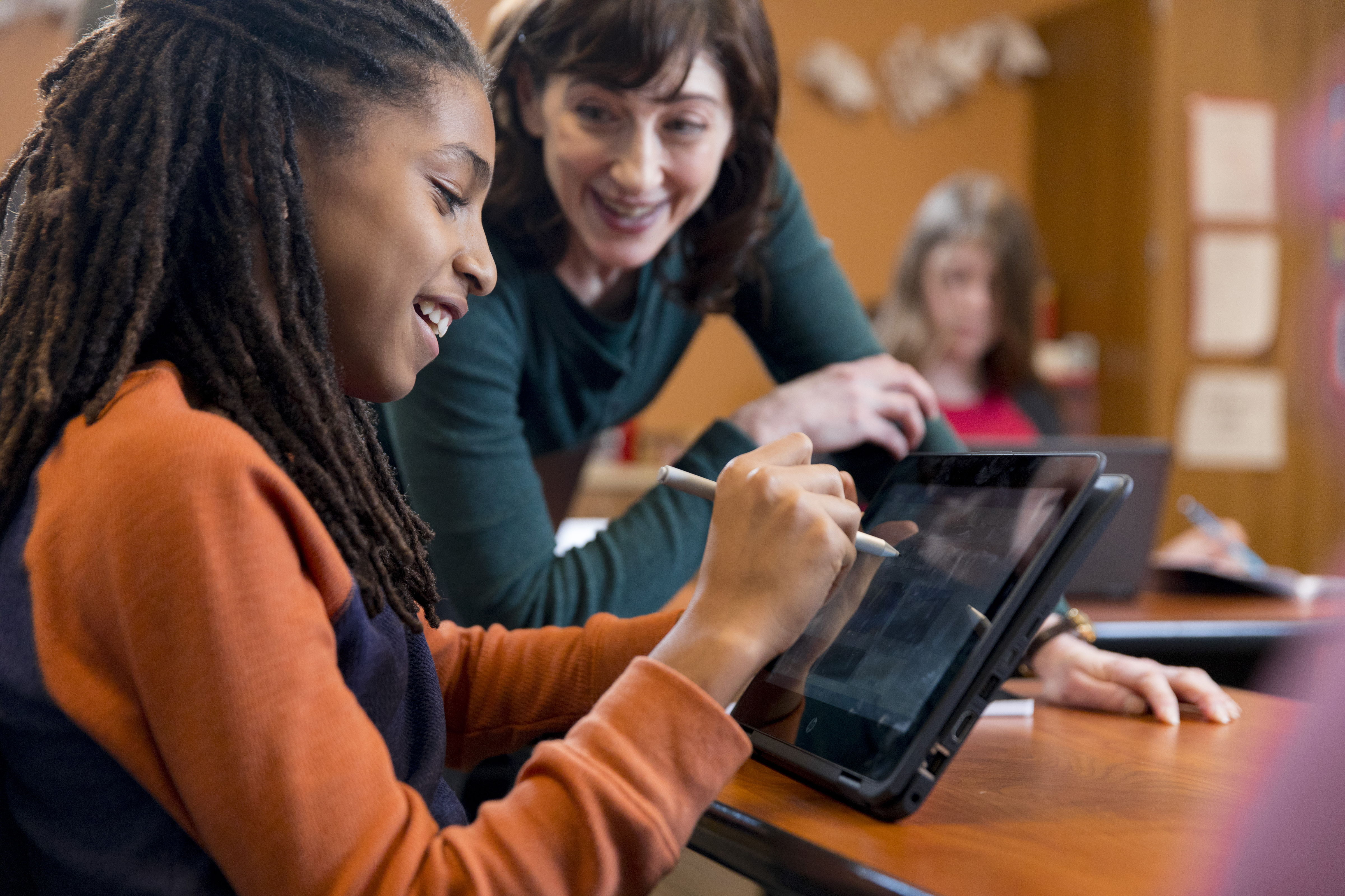 Teacher helping student use a tablet