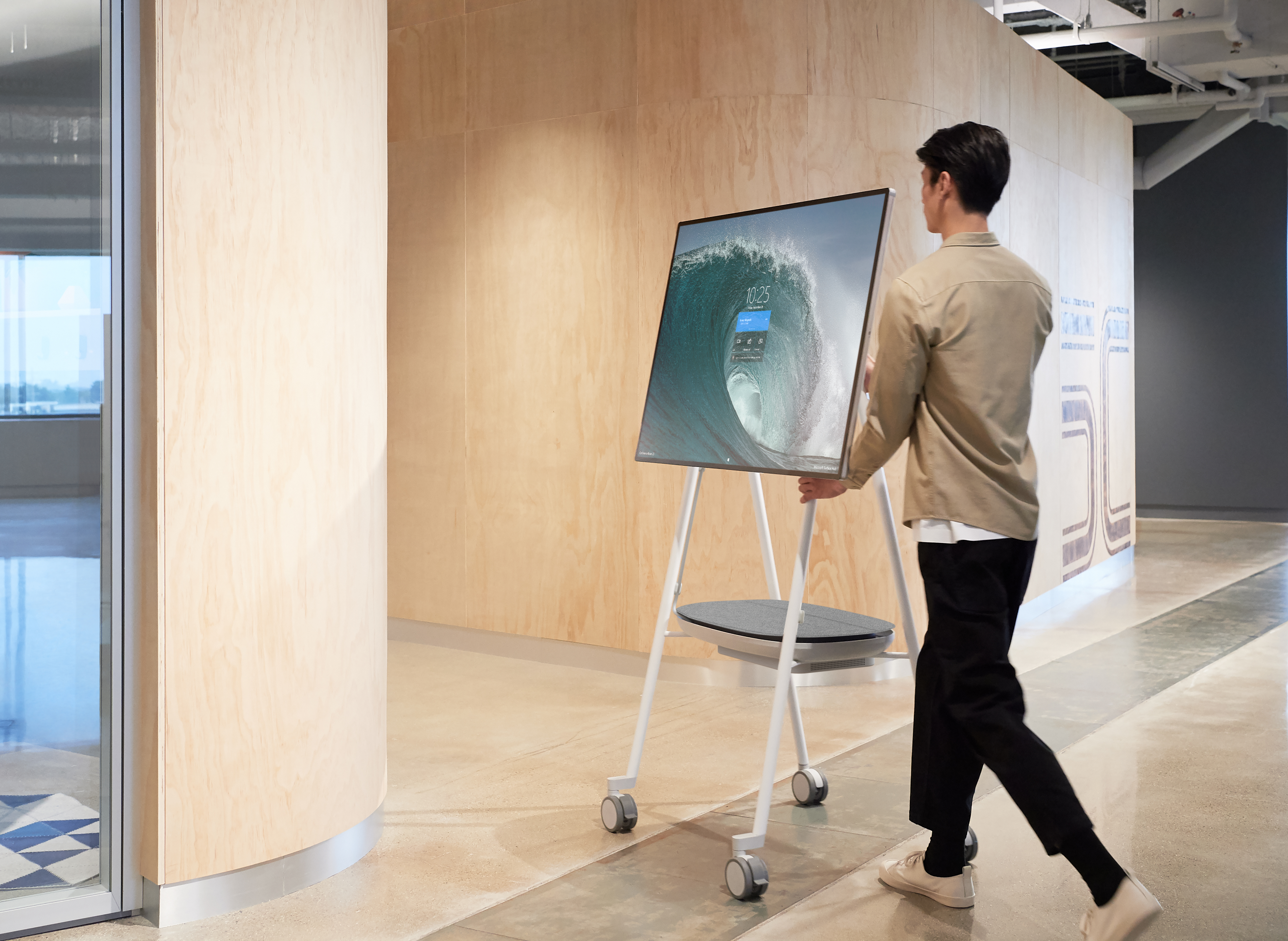A man wheels the SUrface Hub 2S into a room