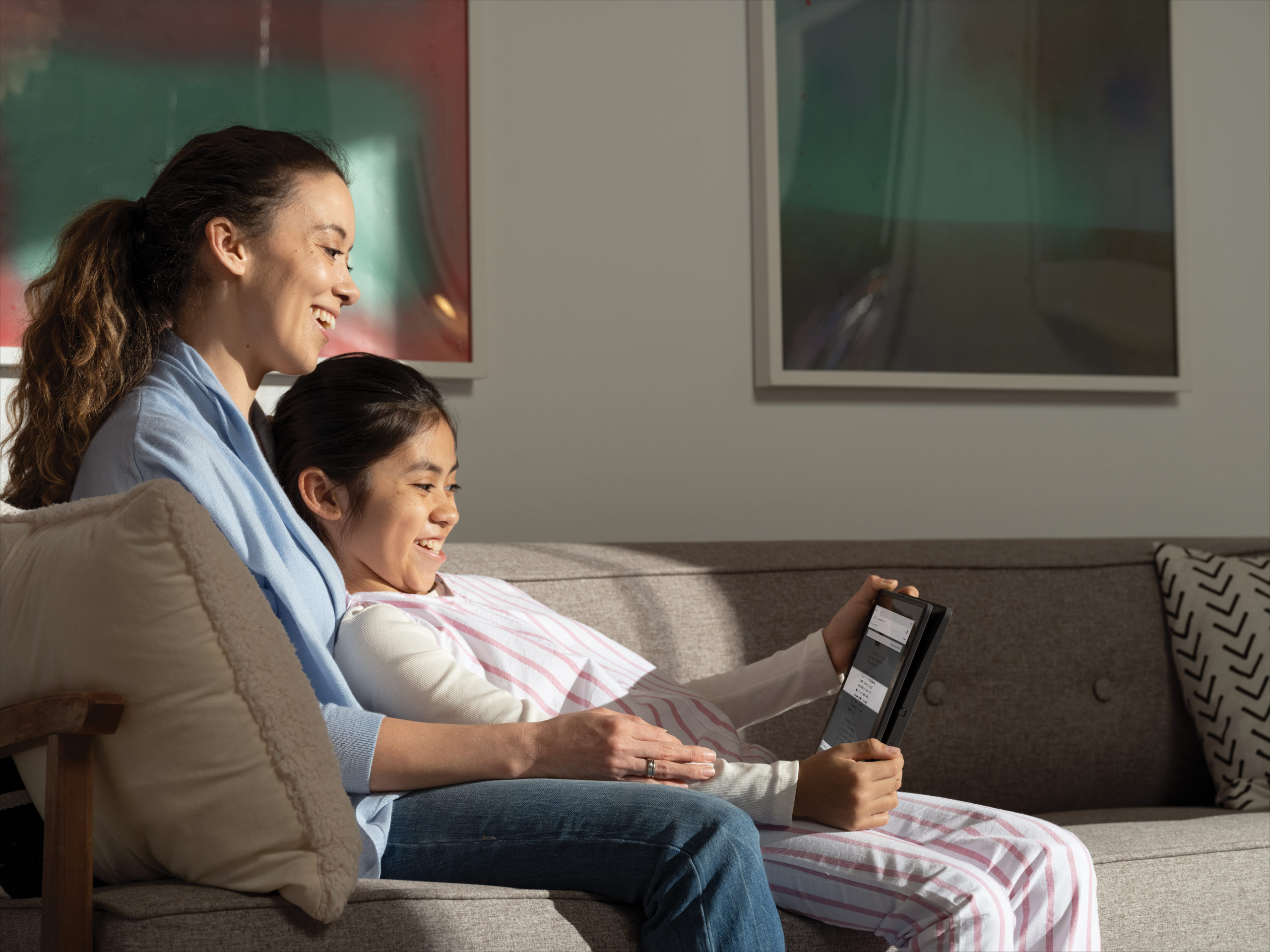 A mother and her daugther reading a webpage with Immersive Reader in Microsoft Edge. The Acer Travelmate B311 2-in-1 is in tablet mode