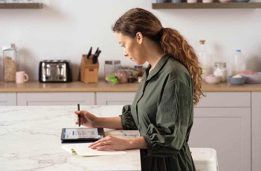 Woman uses a tablet in the kitchen