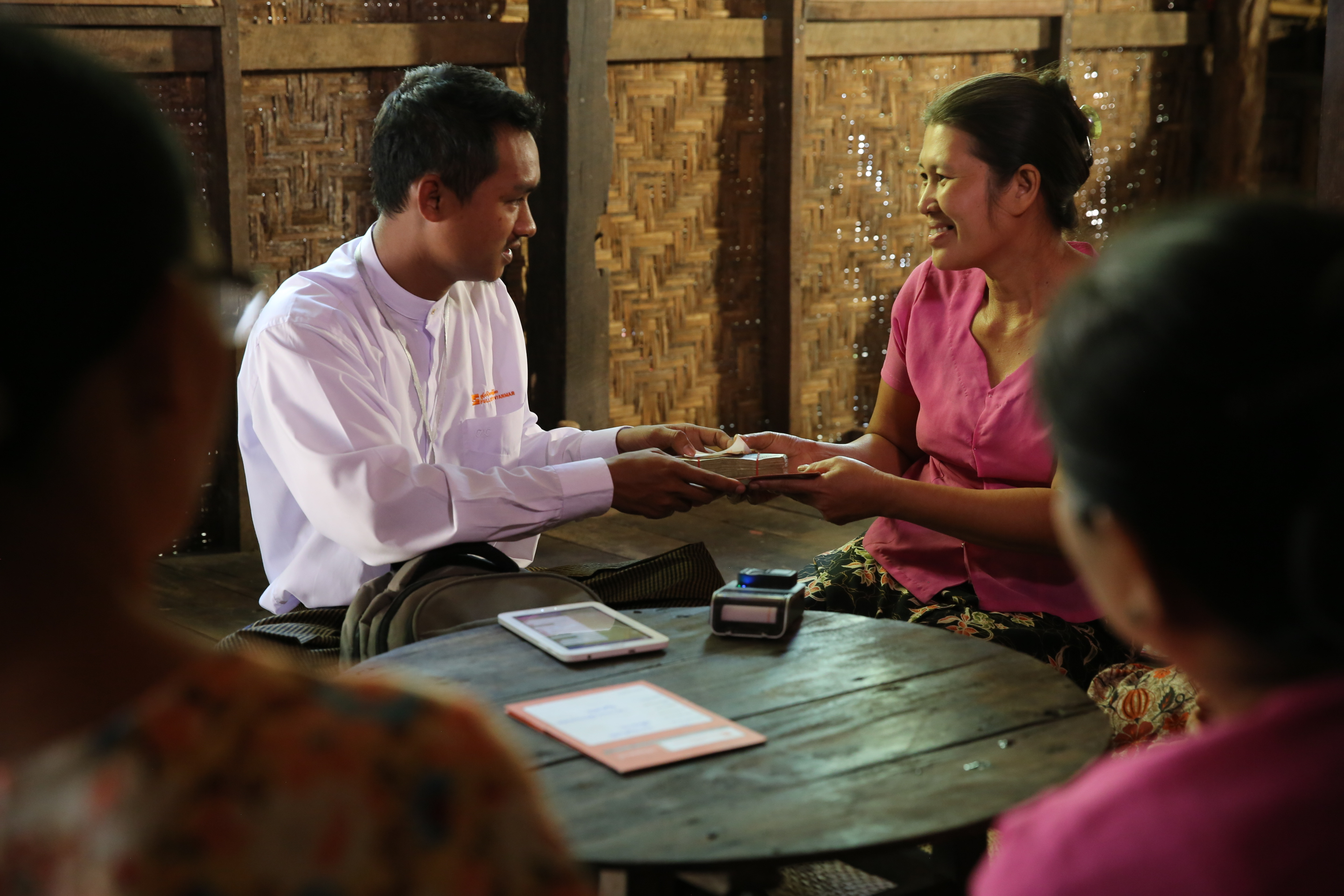 Fullerton Myanmar loan officer Min Thu, left, meets with Win Win Soe, who received a microfinance loan that helped her open a factory that makes noodle snacks.