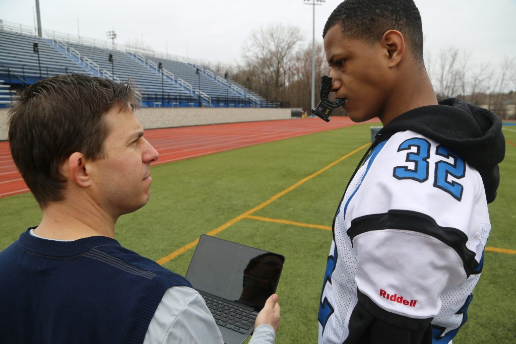 Middletown High School athletic trainer Craig Olejniczak consulting with a player on the team, who is wearing a Vector MouthGuard. (Photo by Kelly Guenther.)