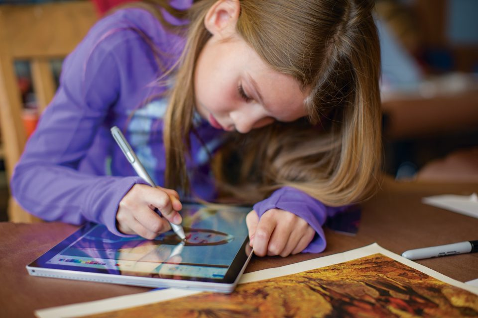 Girl drawing on a Surface Pro 4 in classroom