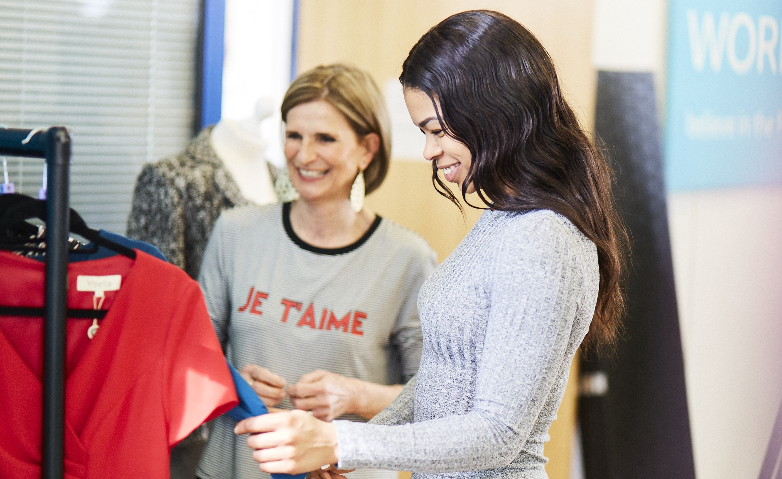 Woman smiling as she looks at clothes at Smart Works